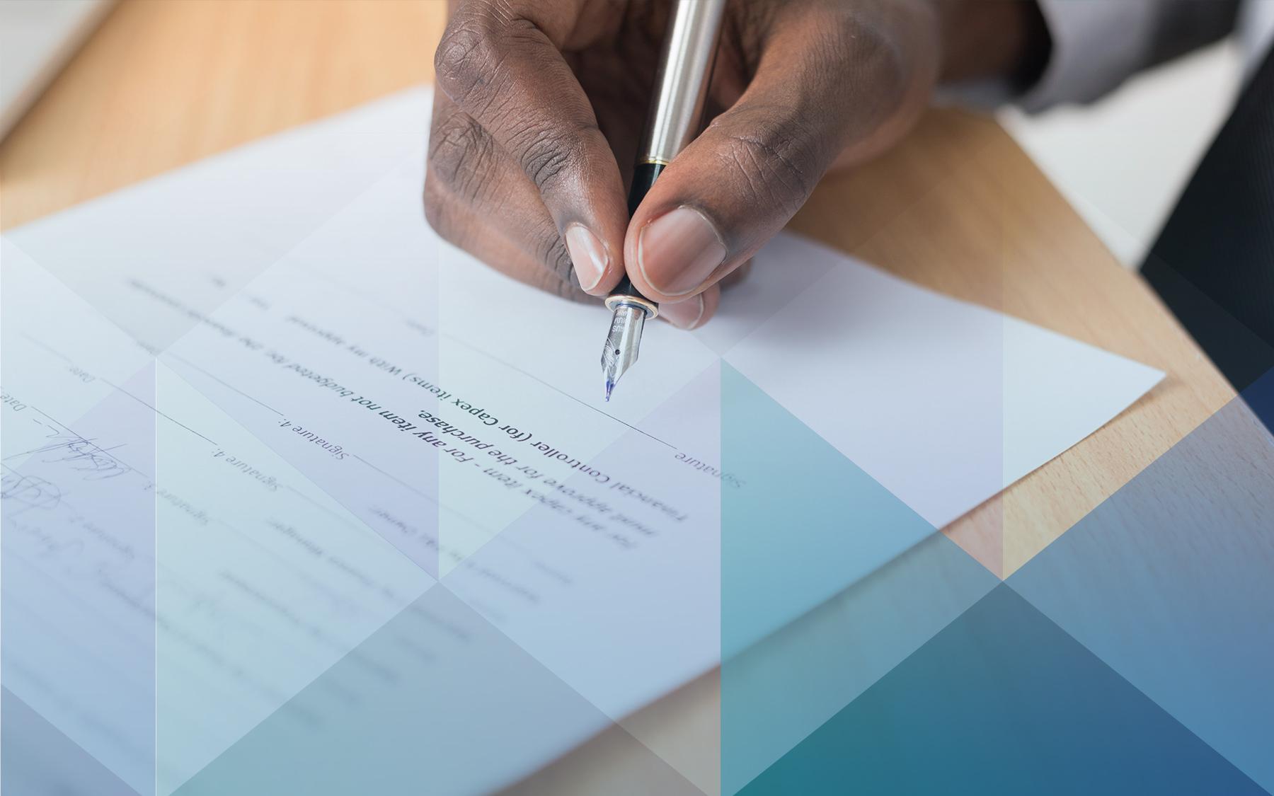 """Imagem de destaque para o texto """"Revisão Contratual"""", mostra a mão de um homem escrevendo em uma folha com uma caneta"""